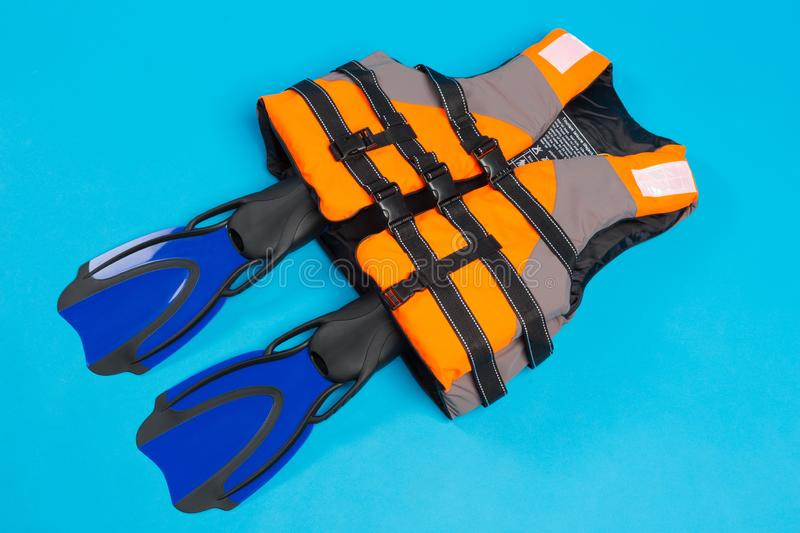 Orange life jacket and pair of blue flippers, on blue background, concept of safe diving and recreation. Flat lay royalty free stock images