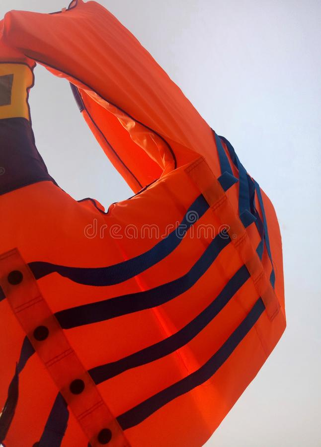 Orange life jacket with a white background. Buoy, bright, closeup, clothing, color, elegance, equipment, fabric, float, isolated, lifejacket, opened, new stock photography