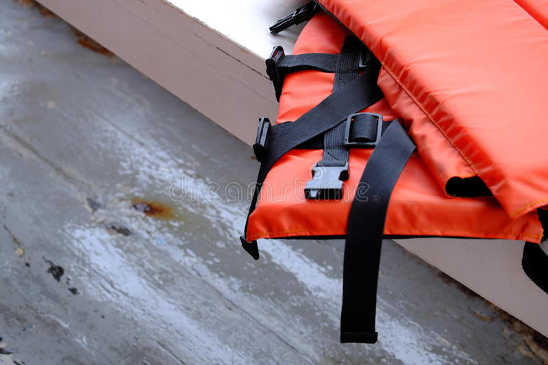 Orange life jacket on white table. Copy space stock photography