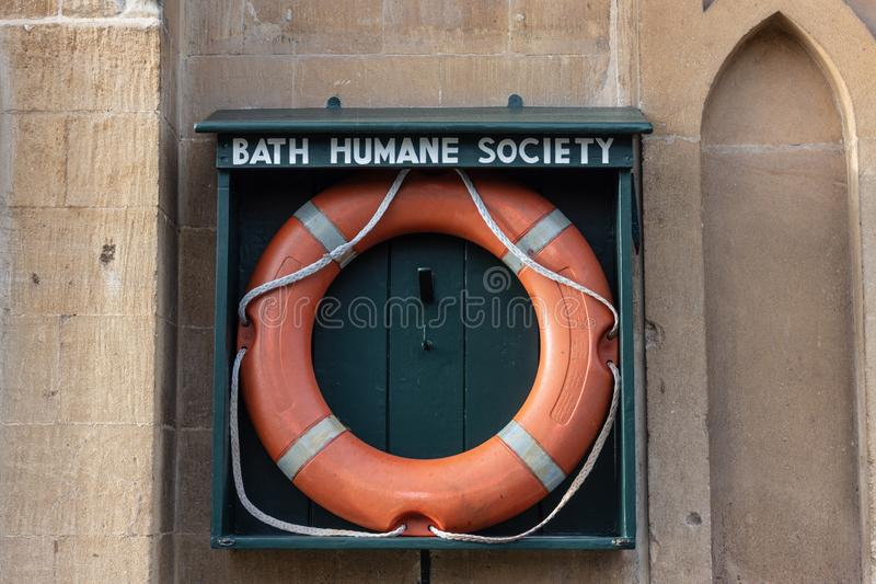 Orange life preserver in Bath Humane Society holder. An orange life preserver in an open wooden holder marked `Bath Humane Society` on a wall next to the Kennet royalty free stock images