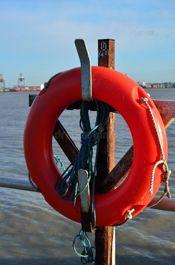 Orange lifebelt at shore. Orange lifebelt at sea shore royalty free stock photography