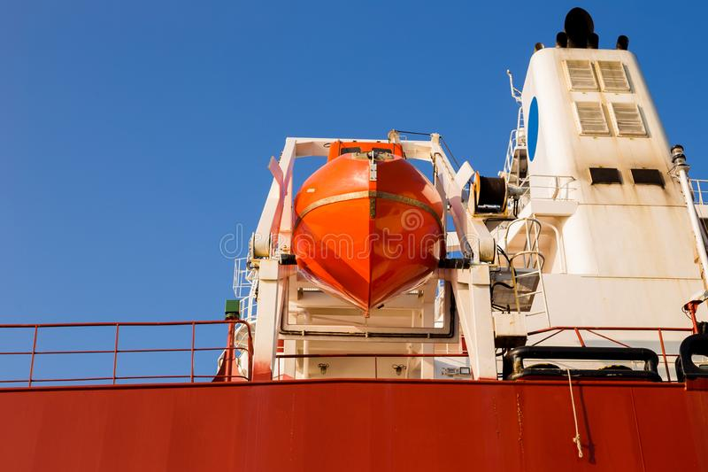 Orange lifeboat at tail of international cargo ship in the ocean for emergency evacuation loading for safety, Freight royalty free stock photography