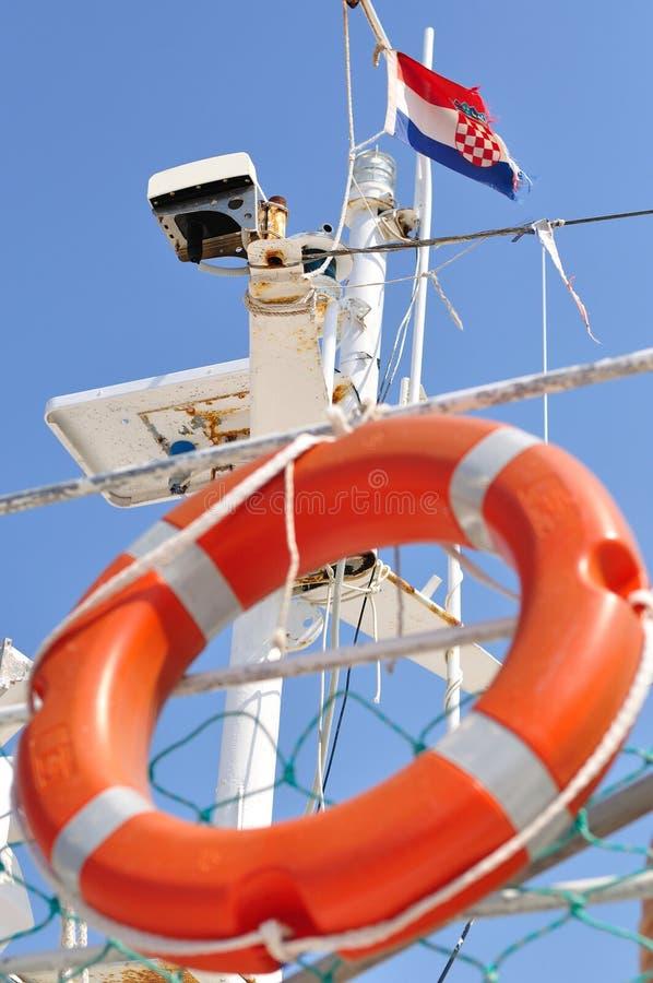 Orange lifebuoy hanging on ship with Croatian flag royalty free stock photography