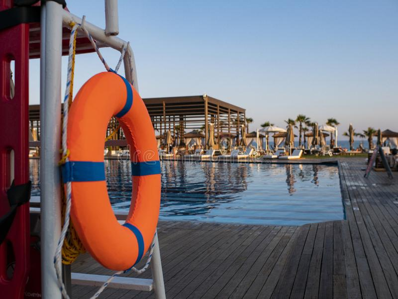 Orange lifebuoy near public swimming pool On a blurred background, a swimming pool is visible royalty free stock image