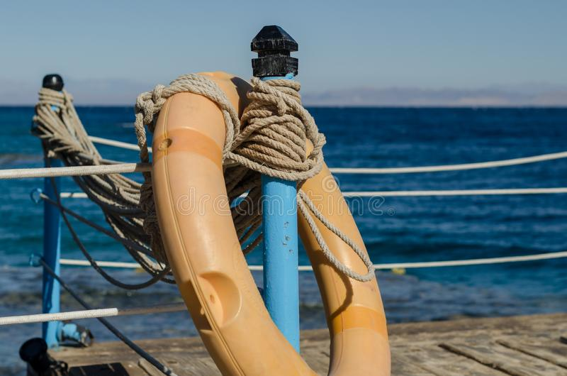 Orange lifebuoy on a wooden table with ropes on a wooden platform on a background of blue sea in Egypt Dahab South Sinai. Orange lifebuoy on a wooden table with stock photography