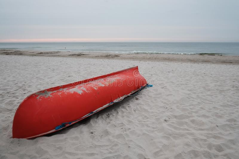 Orange lifeguard`s rescue boat upside down on beach at Baltic coast royalty free stock photo