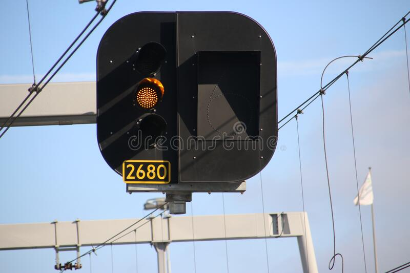 Orange light sign above the rails to let train drivers use low speed at Utrecht Central Station royalty free stock photography