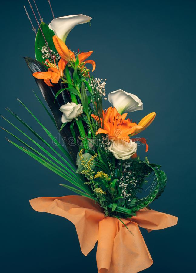 Orange lilies, white calla flowers and palm tree leaves bouquet vertical color image studio shot. Mothers day concept background, stock photo