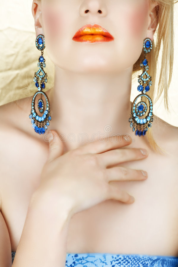 Orange lips and blue earings royalty free stock images