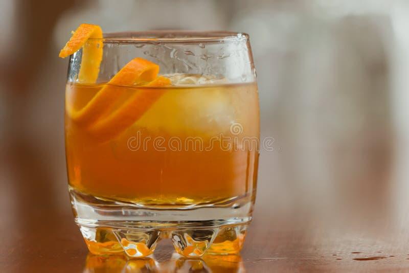 Orange liquor on the rocks. Orange liquor served on the rocks with an orange twist as a garnish stock photography