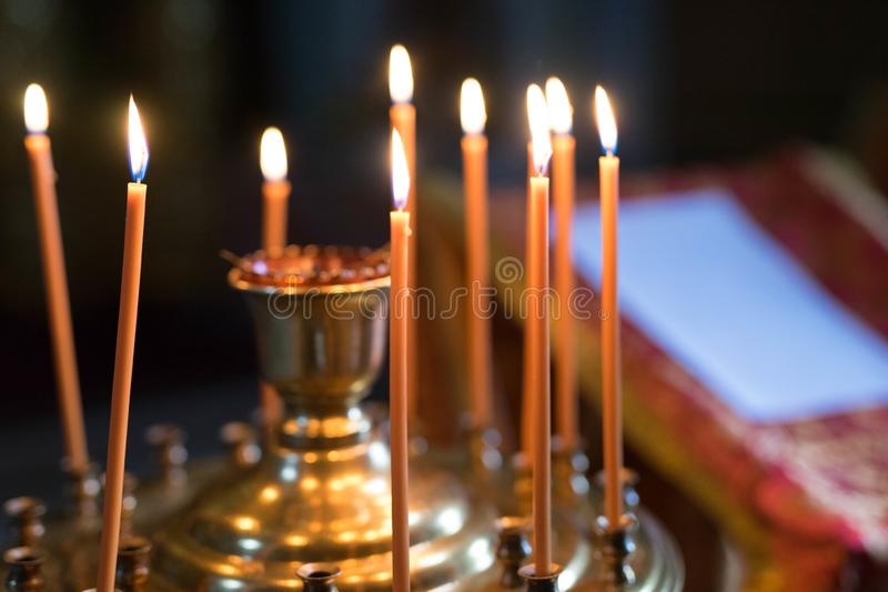 Orange lit candles stand in a candlestick stock photography