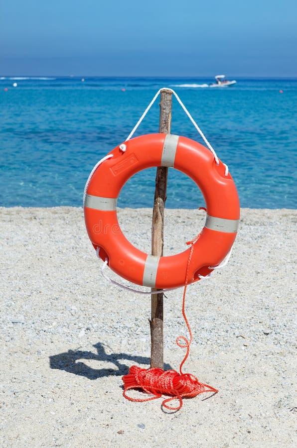Orange livboj på den sandiga stranden mot blått havsvatten royaltyfri bild