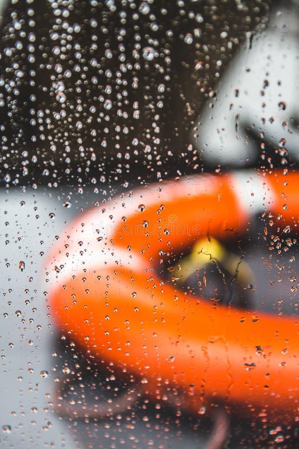 Orange livpreserver på ett fartyg under en regnstorm, grund dep royaltyfria foton