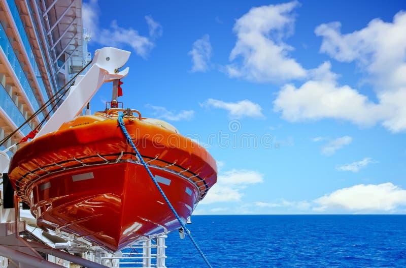 Orange livräddningsbåt som hänger från selet över det djupblå havet arkivbild