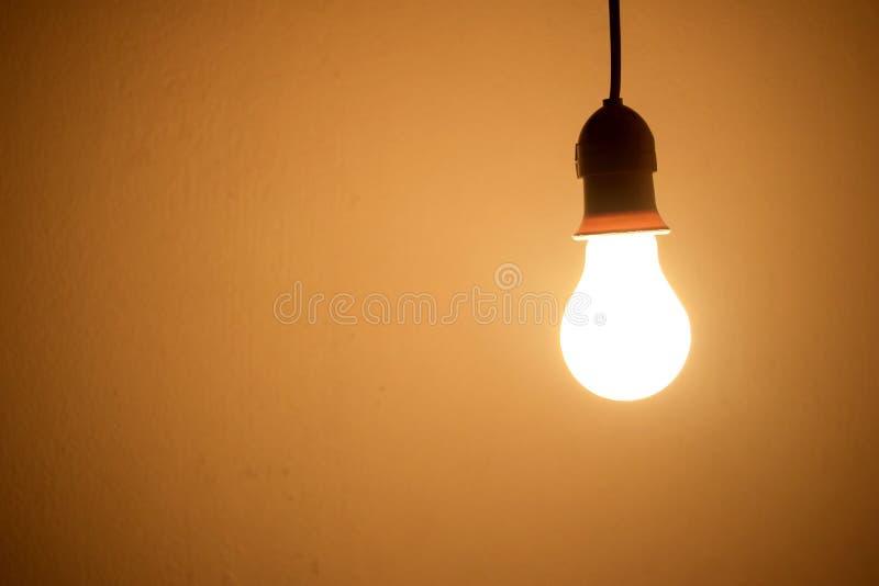 Orange ljus för Lightbulblampa i rum på natten arkivbild