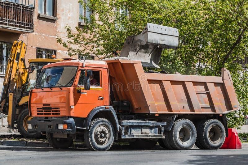 Orange LKW und gelbe Baggerarbeit f?r Reparatur die Asphaltstra?e in einer Stadt im Sommer lizenzfreie stockfotografie