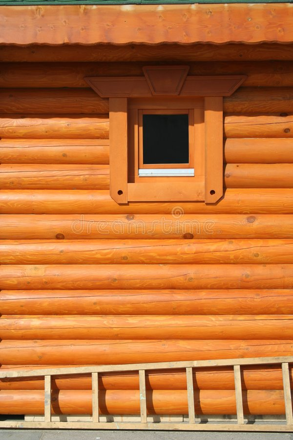 Orange log wall. Orange wooden log wall with small window and a ladder stock photography