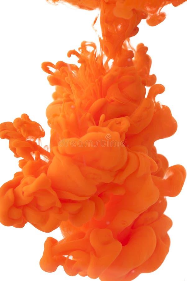 Orange målarfärg i vatten arkivbild