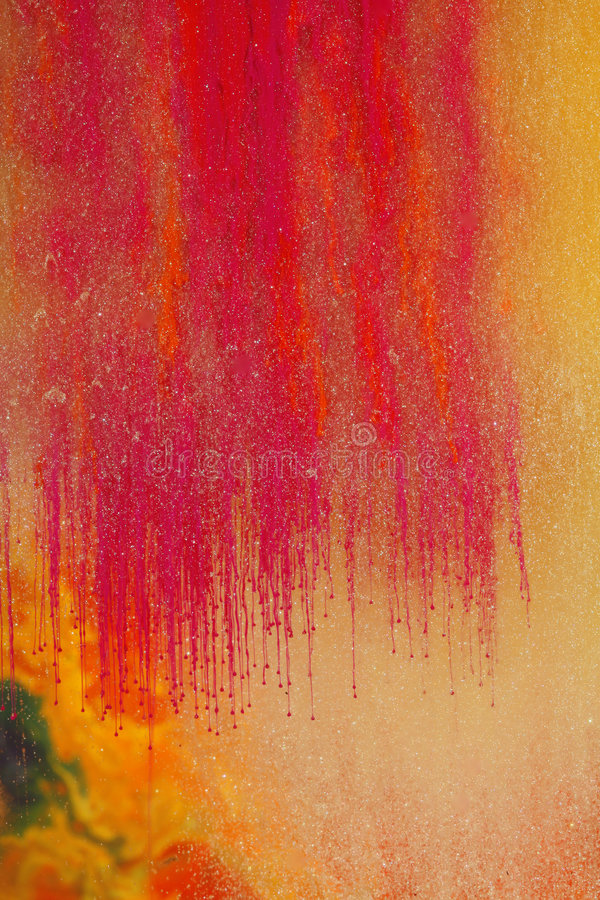 Orange magenta water paints. Orange and magenta paint dissolving in water which is enriched with glittering particles stock photo