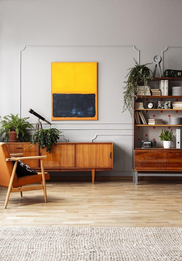Orange Malerei über hölzernem Schrank im Retro- flachen Innenraum mit Lehnsessel und Anlagen Reales Foto stockbilder