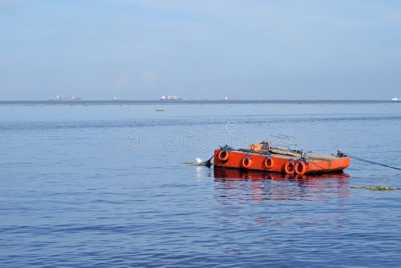 Orange malte Metalllastkahn verankert entlang Ozeanbucht lizenzfreie stockfotografie