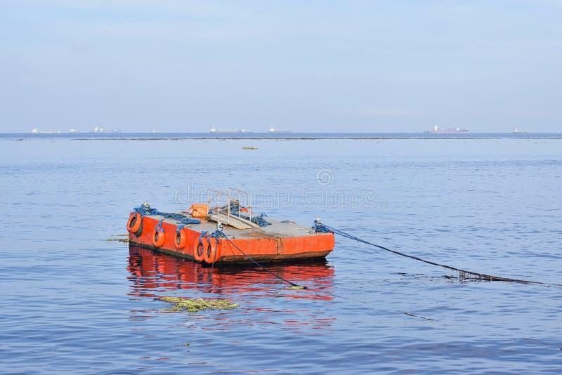Orange malte Metalllastkahn verankert entlang Ozeanbucht stockbild