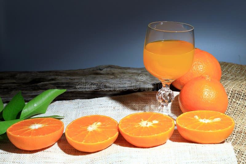Orange mandarin- eller tangerinfrukter, med gröna sidor och apelsinfruktsafter i exponeringsglas på träbrädebakgrund royaltyfria bilder