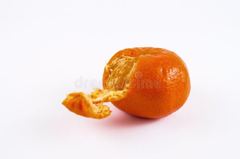 Orange mandarin with peeled one side on a light background royalty free stock photo