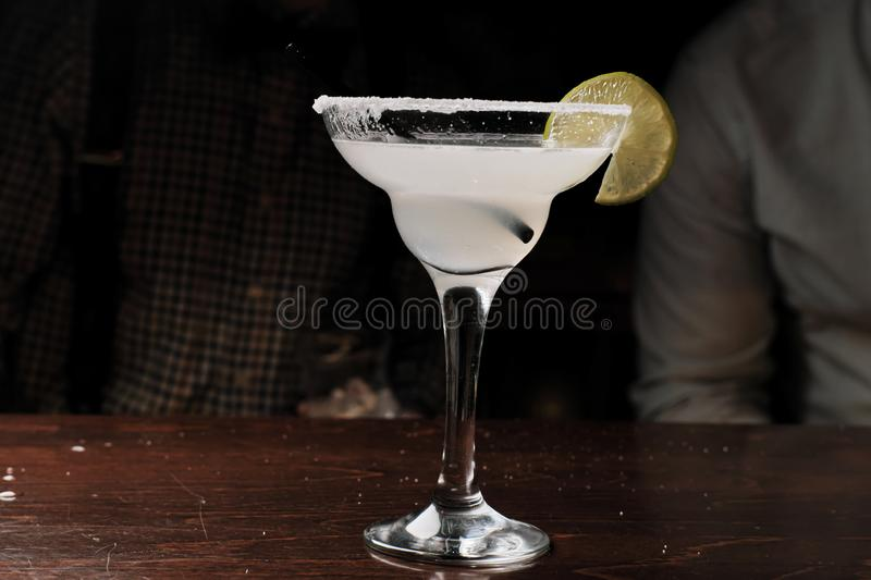 Orange Margarita in chilled glass over black background on reflection surface, garnished with fresh lime and orange stock photo