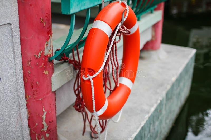 Orange Marinerettungsring auf Pier im Park im selektiven Fokus Werkzeug, zum von Leben auf Wasser zu retten lizenzfreies stockfoto