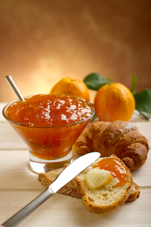 Orange marmalade. Bowl with orange marmalade bread with butter and marmalade and croissant stock images