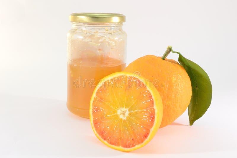 Orange marmalade. Jar of orange marmalade with oranges isolated on white background stock images