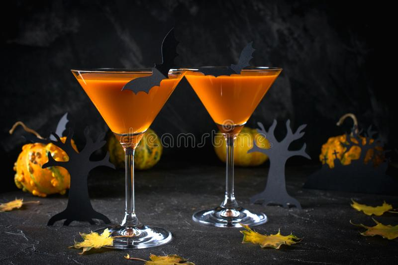Orange martini cocktails with bats and decor for Halloween party, on dark. Background royalty free stock photo