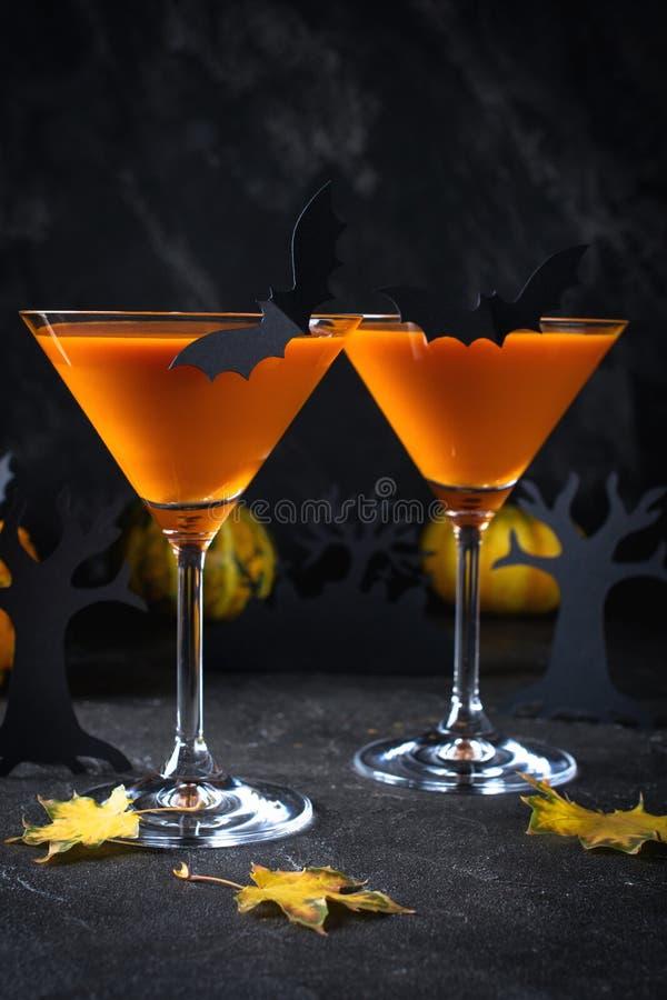 Orange martini cocktails with bats and decor for Halloween party,  on dark background. Orange martini cocktails with bats and decor for Halloween party, on dark stock photos