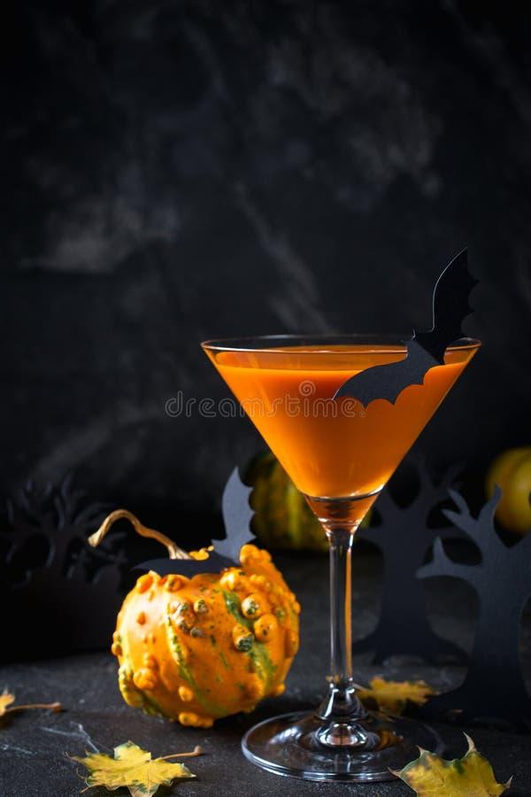 Orange martini cocktails with bats and decor for Halloween  party, on dark background. Orange martini cocktails with bats and decor for Halloween party, on dark stock photo