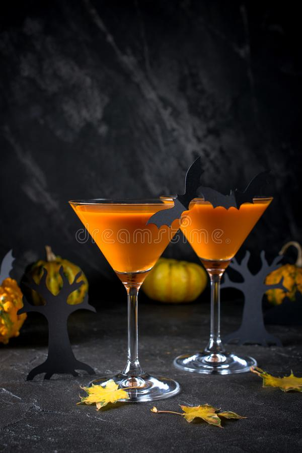 Orange martini cocktails with bats and decor for Halloween party, on dark  background. Orange martini cocktails with bats and decor for Halloween party, on dark stock photography