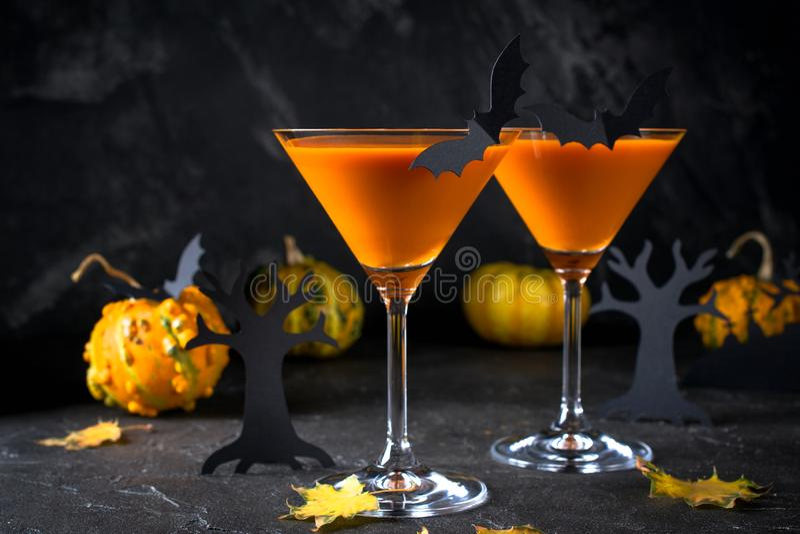 Orange Martini-Cocktails mit Schlägern und Dekor für Halloween-Partei, auf Dunkelheit stockfoto