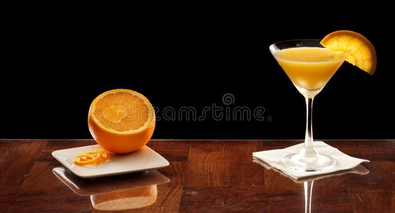 Orange martini with an orange slice. Orange martini on a bar top garnished with an orange slice and fresh orange on the side royalty free stock photography
