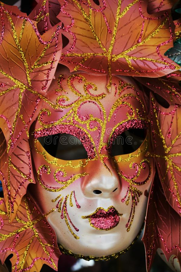 Orange mask, Venice, Italy, Europe. Orange leaves mask with golden arabesques and decorations, in Venice, Italy, Europe royalty free stock image