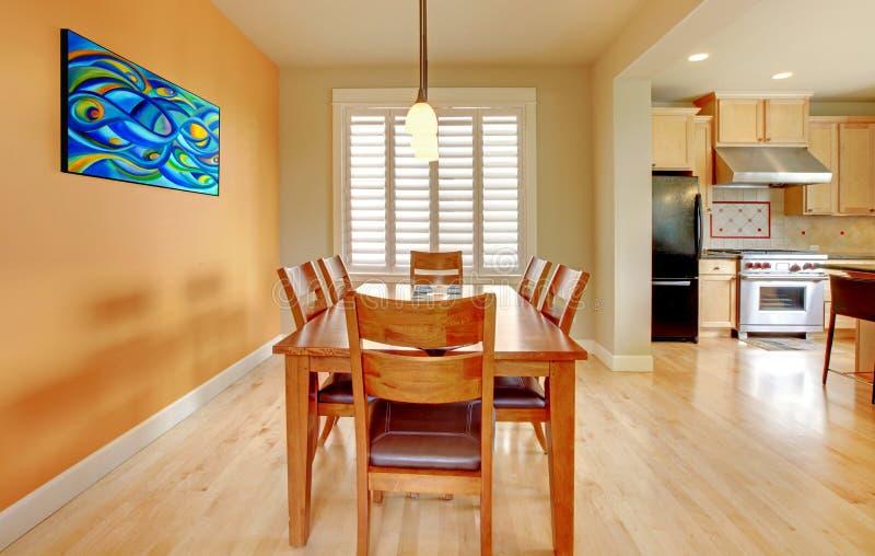 Orange matsal med det wood golvet och kök. arkivfoton