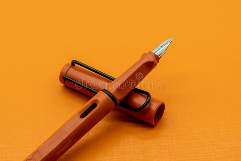 Orange Mattkalligraphisches oder Füllfederhalter auf orange Hintergrund lizenzfreies stockbild