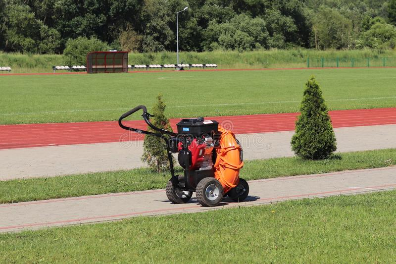 Orange mechanical device for cleaning and the formation of lawn sports objects in the open air against the background of a green. Football field, treadmill royalty free stock photo