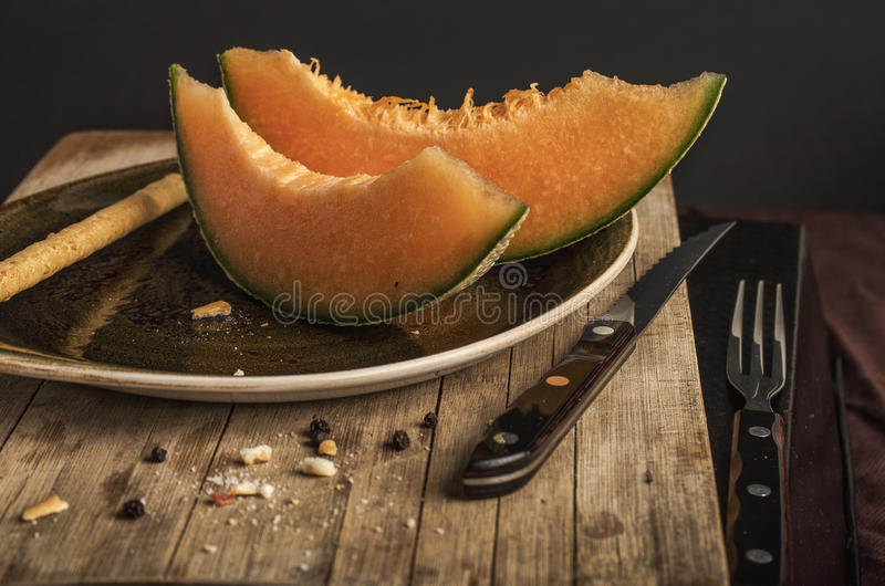 Orange melon black background. Orange melon and bread sticks close up on wooden texture and black background royalty free stock photo
