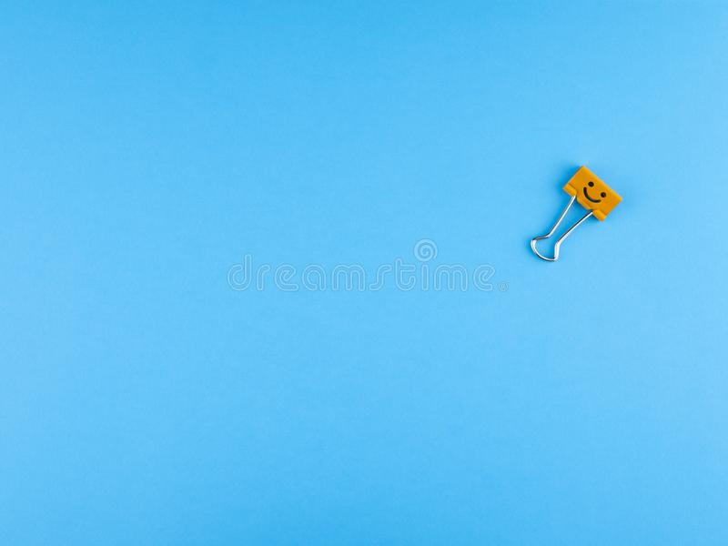 Orange metal binder clip or multicolored paperclip on blue background. With copyspace for text royalty free stock photo