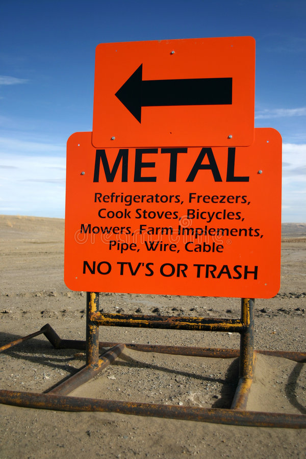 Orange Metal Junk Sign. An orange sign you would see at a public dump or landfill. Reads Metal this way. No TV's or Trash. Great for illustrating a throw away stock image