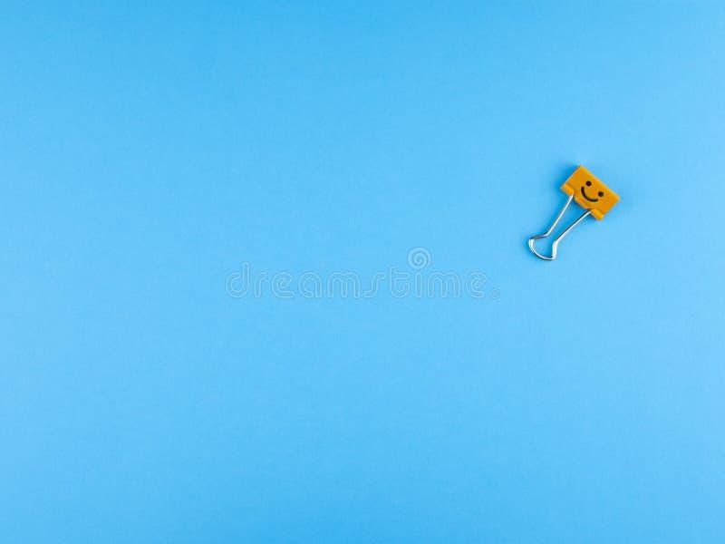 Orange Metallmappenclip oder mehrfarbige Papierklammer auf blauem Hintergrund lizenzfreies stockfoto