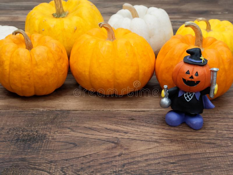 Orange miniature ceramic pumpkin head magician wearing black hat with white, yellow, and orange pumpkins royalty free stock images