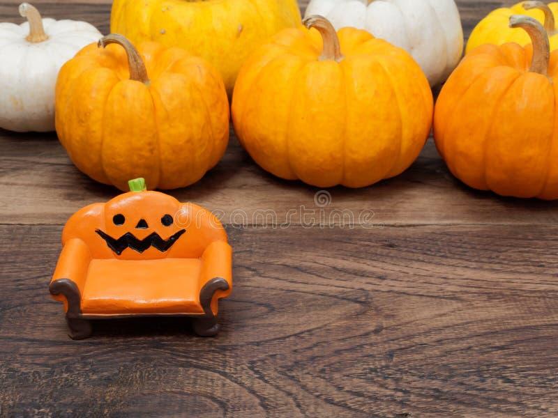 Orange miniatyrkeramisk pumpasoffa eller soffa med vit, guling och orange pumpor på bakgrunden royaltyfria foton