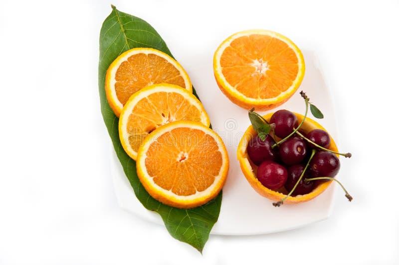 Orange mit Kirsche stockbild