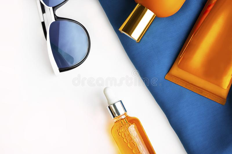 Orange mock up bottles of sun screen and sunglasses on bright contrast blue beach wrap on horizontal empty white background with royalty free stock photography